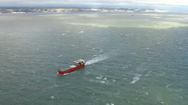 Exterior aerial shots of the Sega Sky cargo ship at sea in choppy waters surrounded by a tug boat and an RNLI rescue vessel after it began taking on...