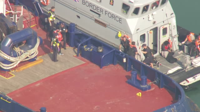 exterior aerial shots of uk border force vessel with rescued migrants and woman carrying small child being escorted from the boat at the port on 27th... - refugee stock videos & royalty-free footage