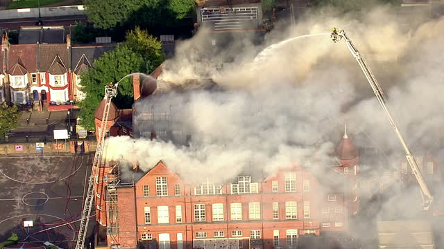 Exterior aerial shots of white smoke billowing from the burnt out roof of St Joseph's Primary School as firefighters spray water onto it from cherry...