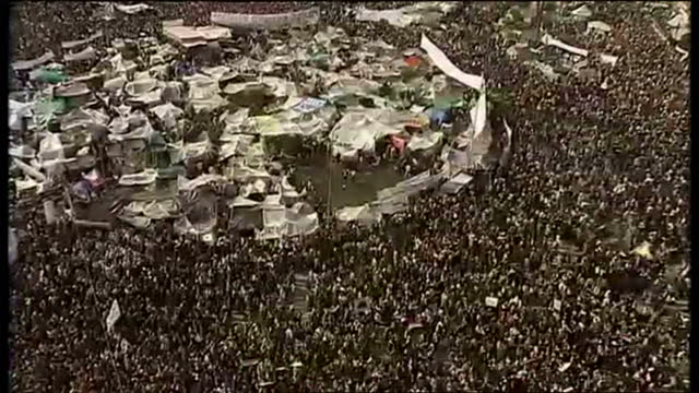 vídeos de stock, filmes e b-roll de exterior aerial shots pan across tahrir square showing thousands of protesters swarming the area thousands gather in tahrir square on february 11... - arab spring