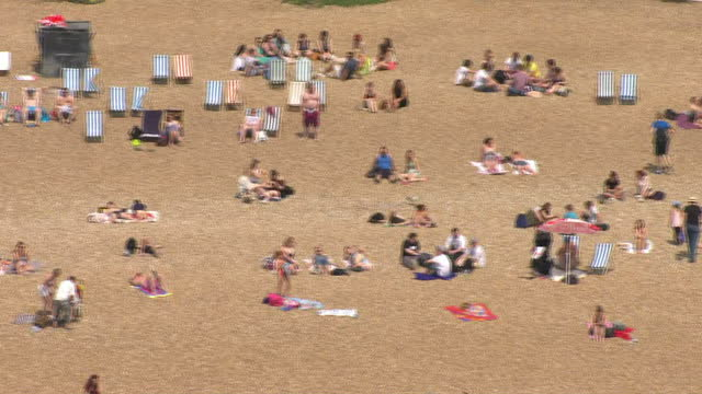 exterior aerial shots people sunbathing and relaxing on brighton beach on hot sunny day. on july 01, 2015 in brighton, england. - sunny video stock e b–roll