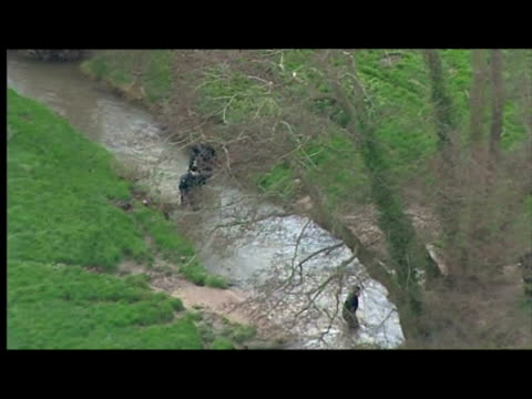 exterior aerial shots police divers, detectives in wetsuits searching in & alongside stream, river - investigatore video stock e b–roll