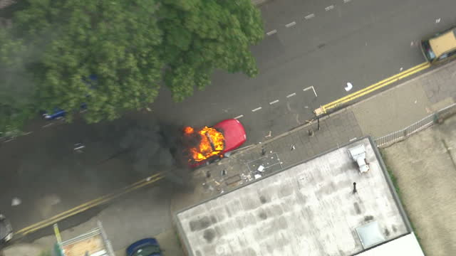 vidéos et rushes de exterior aerial shots red sports car engulfed in flames in hackney. aerial shots gang of rioters gathered on main road. hackney riots aerials on... - hackney
