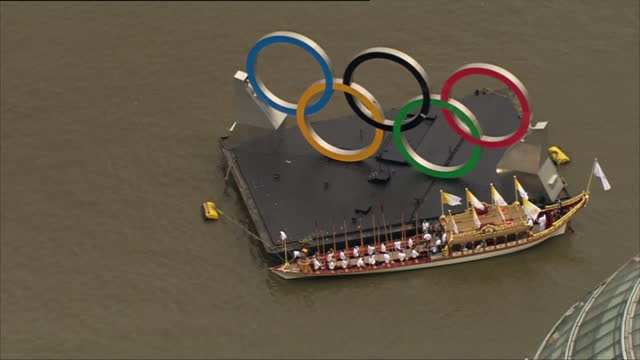 exterior aerial shots the gloriana row barge moors up by the large olympic rings logo alongside city hall with the torch cauldron burning at its bow... - 2012年ロンドン夏季オリンピック点の映像素材/bロール