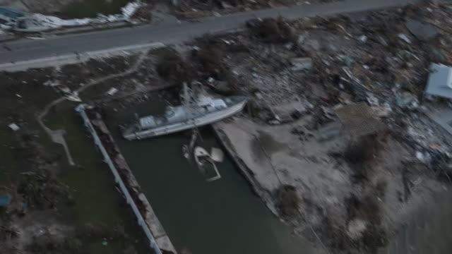 exterior aerial views of destruction caused by hurricane dorian in the bahamas, showing devastation in the harbour area, including boat half out of... - バハマ点の映像素材/bロール
