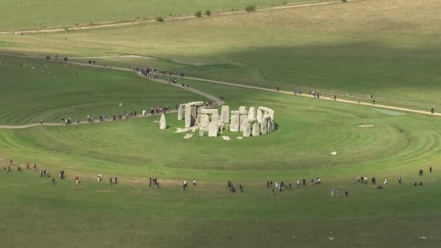 exterior aerial views of stonehenge, with tourists looking from behind perimeter fence viewing area, including zoom in to stones on 13 september 2018... - prehistoric era stock videos & royalty-free footage