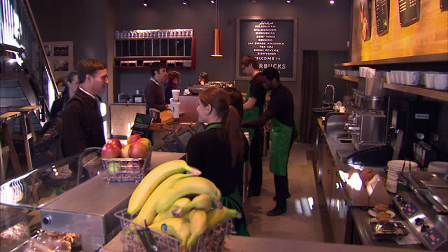 vídeos de stock, filmes e b-roll de exterior and interior shots of strarbucks coffee shop cafe withj people serving drinks starbucks coffee store at knightsbridge on march 08 2011 in... - starbucks