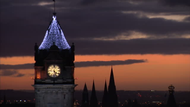 Exterior arty shot of the Clocktower of the Balmoral Hotel with Christmas lights on top of it pan to Edinburgh Castle at sunset with purple sky in...