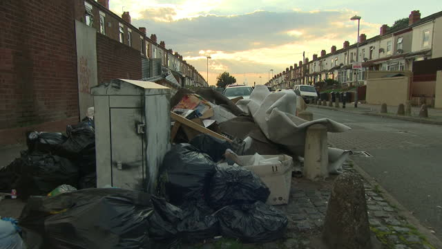 exterior arty shots of piled up rubbish bins that are overflowing with uncollected rubbish due to the refuse worker strike in birmingham at sunset... - unhygienisch stock-videos und b-roll-filmmaterial