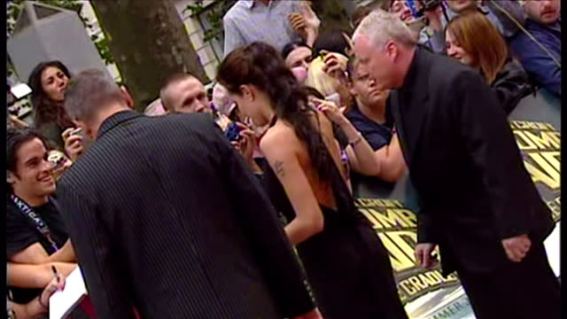 Exterior back views of Angelina Jolie signing autographs for fans lots of shots of her tattoos