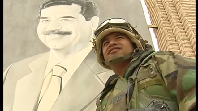 exterior close shots of an american soldier stood in front of a poster of saddam hussein in umm qasr. us troop stands next to saddam hussein poster... - iraq stock videos & royalty-free footage