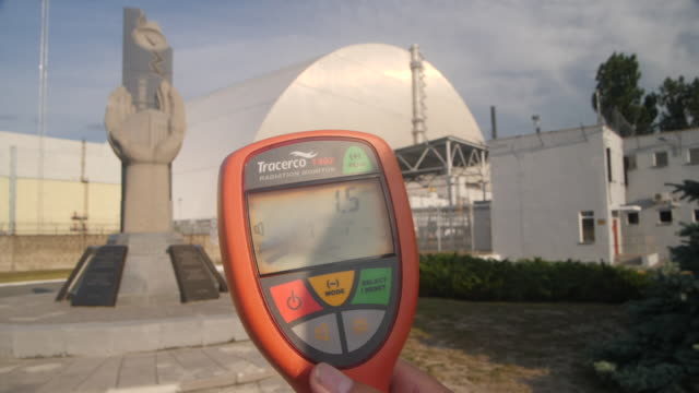 exterior close up shot of a hand held radiation monitor or 'geiger counter' showing a reading of background radiation with the chernobyl reactor 4... - contatore geiger video stock e b–roll