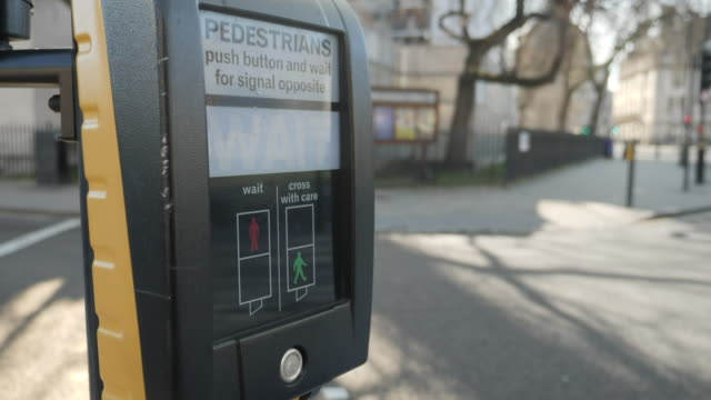 exterior close up shot of a pedestrian crossing button with a blurred background of light traffic travelling through westminster, london during the... - pedestrian crossing stock videos & royalty-free footage