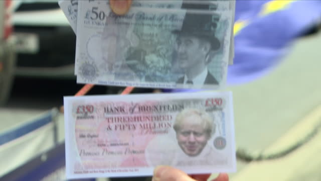 exterior close up shots of anti brexit protesters holding fake banknotes with a picture of boris johnson during a demonstration outside the houses of... - brexit stock videos & royalty-free footage