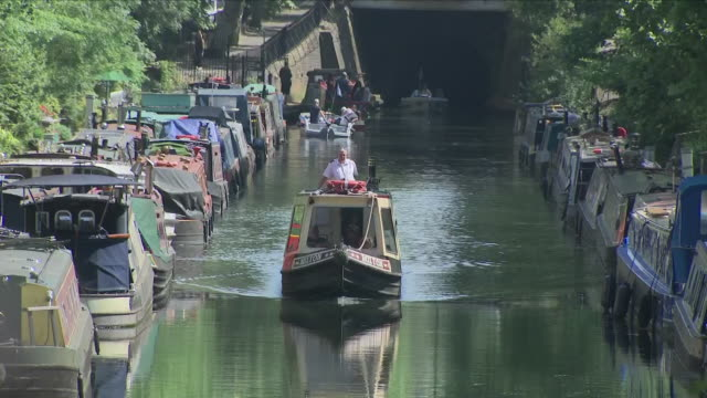 vídeos de stock e filmes b-roll de exterior close up shots of canal boats and small boats going along regent's canal past houseboats parked up in little venice including shots of... - barco casa