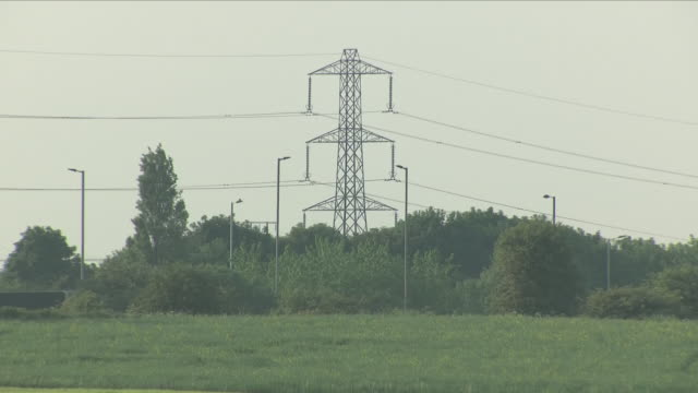 exterior close up shots of electricity pylons in fields in slightly foggy weather on 3rd june 2018 in nottinghamshire east midlands united kingdom - electricity pylon stock videos and b-roll footage