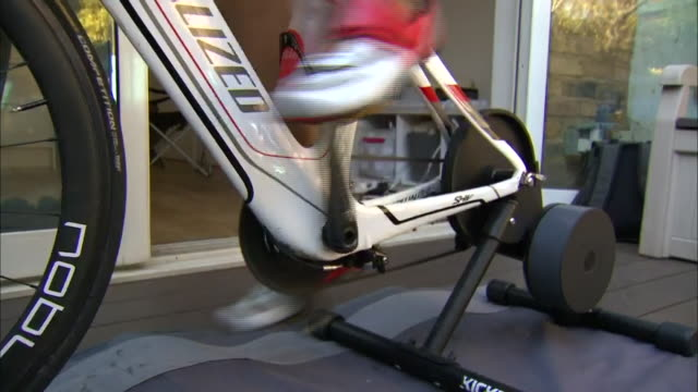 exterior close up shots of neil clarke cycling on an exercise bike in the garden, as he takes on the first phase of his garden triathlon, on the 19th... - phase image stock videos & royalty-free footage