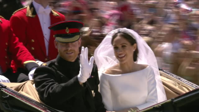 Exterior close up shots of Prince Harry and Meghan Markle waving to crowds during their carriage procession along The Long Walk after the wedding...
