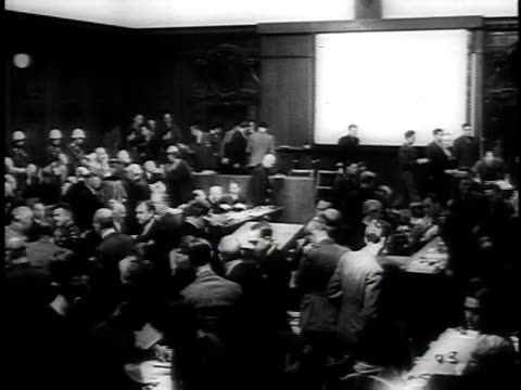 exterior court / accused walking into courtroom / nazis sitting with guards behind them / man testifying / ws courtroom - processi di norimberga video stock e b–roll