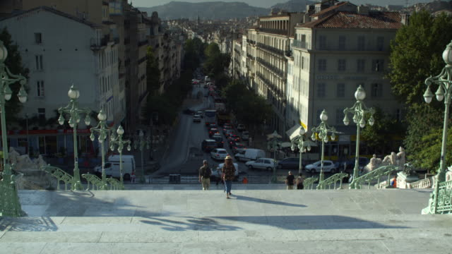 vidéos et rushes de exterior day pan shot of steps leading down into the street from a train station in marseille.  overlooks the street below with cars and people walking by.  - marseille