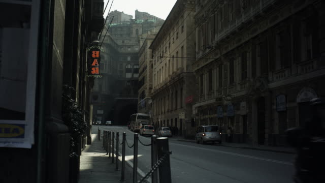 exterior day shot of a moderatly busy street with cars passing by in genoa, italy. travel destination  - inquadratura fissa video stock e b–roll
