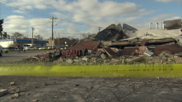 exterior day shots of damaged caused by looters rioters in ferguson smoke rising from smouldering rubble dime beauty store heap of rubble with police... - dime stock videos and b-roll footage