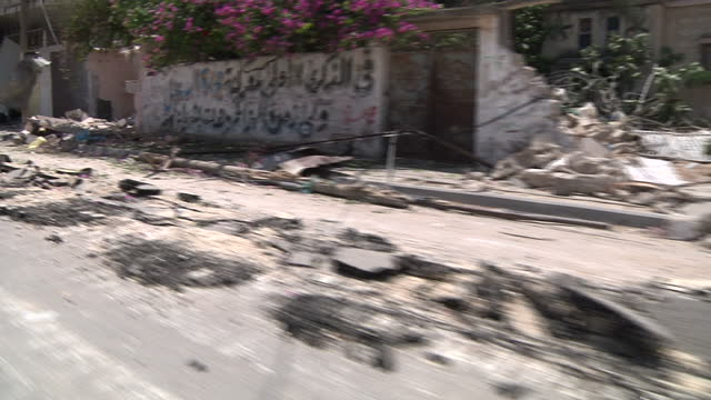 exterior driving shot along a road in gaza alongside rubble and a road which has been damaged by an israeli tank on july 26, 2014 in gaza city, gaza. - パレスチナ自治区点の映像素材/bロール