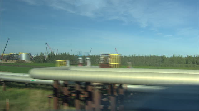 Exterior driving shot alongside Keystone XL oil pipeline depot in Alberta Canada with various oil storage and processing tanks and a section of...
