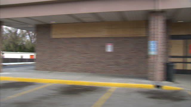 exterior driving shot through downtown ferguson past various boarded up shops in the wake of rioting following the police shooting of michael brown... - missouri stock videos and b-roll footage