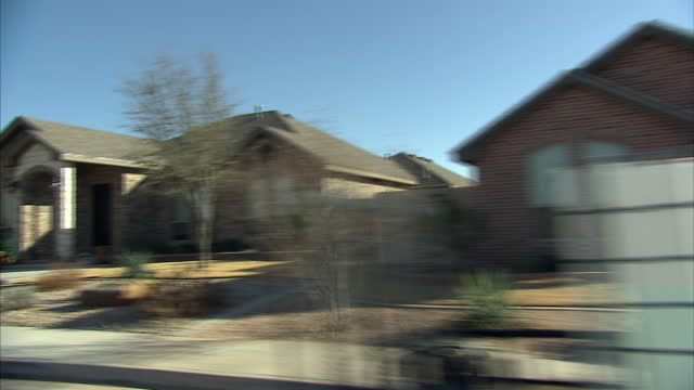 vidéos et rushes de exterior driving shots along a road of nearly completed new houses with builders working on them followed by a road of older established suburban... - récession