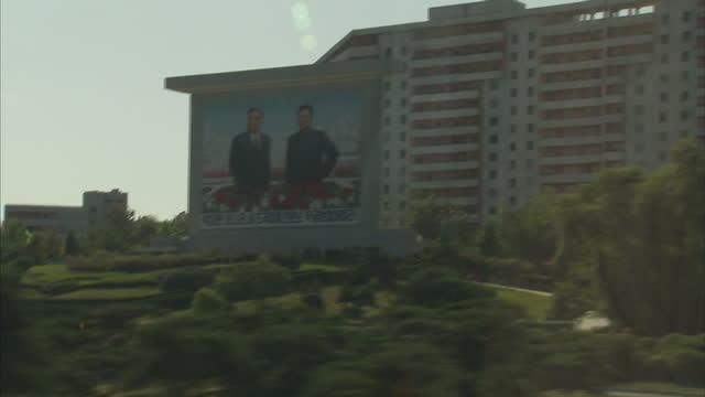exterior driving shots past pyongyang buildings and propaganda posters depicting former north korean leaders kim il sung and kim jong il on october... - propaganda bildbanksvideor och videomaterial från bakom kulisserna