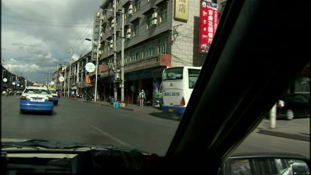 vídeos de stock, filmes e b-roll de exterior driving shots through lhasa tibet past a chinese military convoy tibetan people on motorbikes modern chinese advertising signs and tibetan... - autoimolação