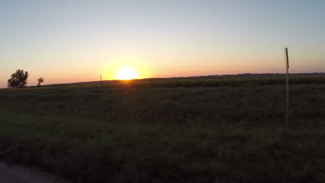 exterior driving shots through rural nebraskan countryside past fields of maize crops, as the sun sets behind distant hills on september 19, 2014 in... - willie nelson stock-videos und b-roll-filmmaterial