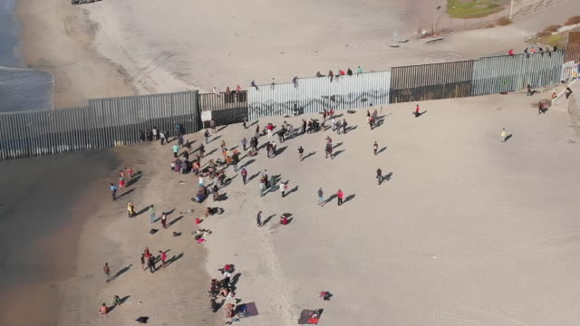 exterior drone aerial shots and general shots of migrants crowding and climbing a border fence on 13 november 2018 in tijuana mexico - border stock videos & royalty-free footage