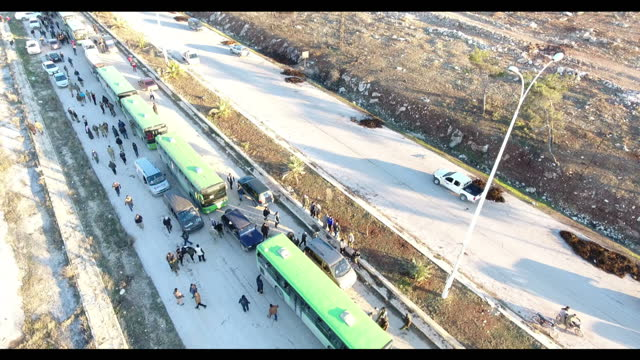 exterior drone aerial shots of a line of buses and refugees leaving eastern aleppo on december 16 2016 in aleppo syria - シリア難民問題点の映像素材/bロール