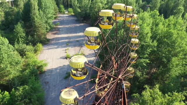 stockvideo's en b-roll-footage met exterior drone aerial shots of decaying, abandoned dodgem cars and ferris wheel at an amusement park on 12 june 2019 in pripyat, ukraine - botsauto