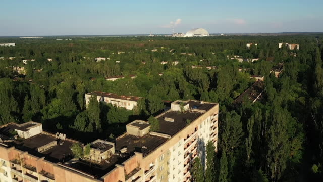 exterior drone aerial shots of the chernobyl reactor four sarcophagus and abandoned housing blocks on 11 june 2019 in pripyat, ukraine - ukraine stock videos & royalty-free footage