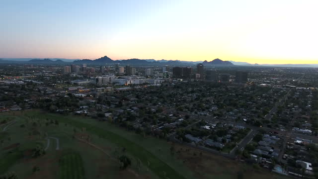 exterior drone aerial shots of the phoenix skyline at sunrise with the sun rising over desert hills, encando park and tower blocks of the downtown... - phoenix arizona stock videos & royalty-free footage