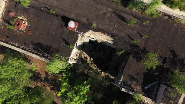 vídeos de stock, filmes e b-roll de exterior drone aerial shots over derelict decaying buildings in pripyat surrounded by overgrown forest moving towards the new sarcophagus over... - moving activity