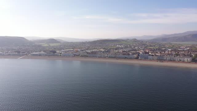 exterior drone aerial shots over llandudno pier on a calm, sunny day - pier is closed due to the coronavirus lockdown, with llandudno shore and beach... - sunny video stock e b–roll