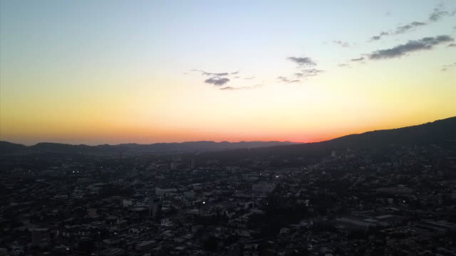 Exterior drone aerial shots over San Salvador city including the business district roads traffic a large cemetery mountains sunset and sunrise on...