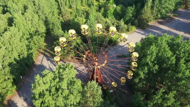 stockvideo's en b-roll-footage met exterior drone aerials around a derelict funfair with dilapidated ferris wheel and dodgem cars on 12 june 2019 in pripyat, ukraine - botsauto