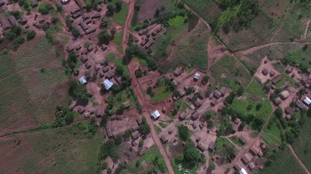 exterior drone aerials of a rural village in malawi, moving over dwellings and surrounding fields and crops, with villagers walking on 2 february... - tradition stock videos & royalty-free footage