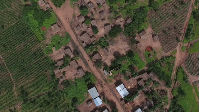 Exterior drone aerials of a rural village in Malawi moving over dwellings and surrounding fields and crops with villagers walking on 2 February 2017...