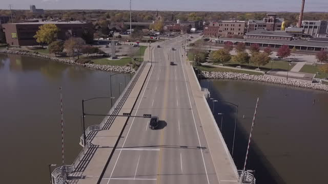 Exterior drone aerials of the Fox River with traffic passing over a bridge and a statue of a Green Bay Packers football player outside a historic...