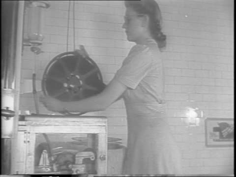 exterior entrance of paramount pictures studios / cast and crew work on movie sets / woman watches 35mm film running through a bath / a woman opens a... - anno 1943 video stock e b–roll
