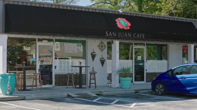 Exterior establishing shot of local restaurant San Juan Cafe with girl sitting in car talking on phone.