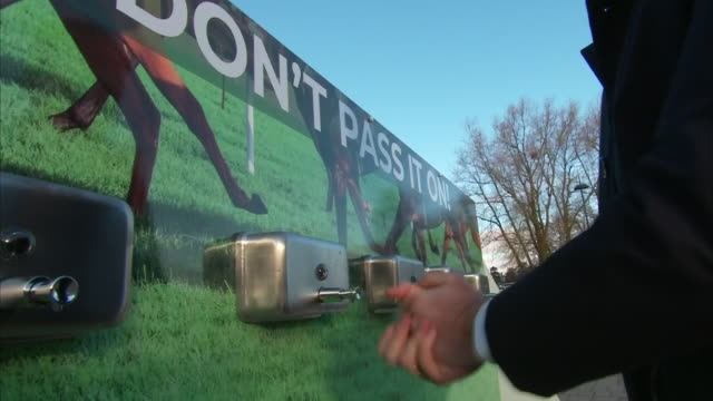 exterior footage of a visitor to the cheltenham festival using a hand santiser station to combat coronavirus, horses walking around the track and of... - cheltenham stock videos & royalty-free footage