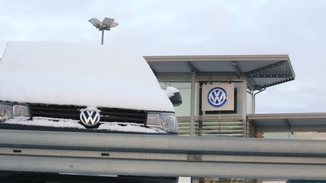 Exterior footage of a Volkswagon Dealership displaying signage and automobiles produced by Volkswagen AG on the forecourt of an Audi showroom in...
