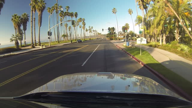 exterior gopro shots aboard car driving along santa barbara ocean front area at sunset past palm trees on february 06 2013 in santa barbara california - santa barbara bildbanksvideor och videomaterial från bakom kulisserna